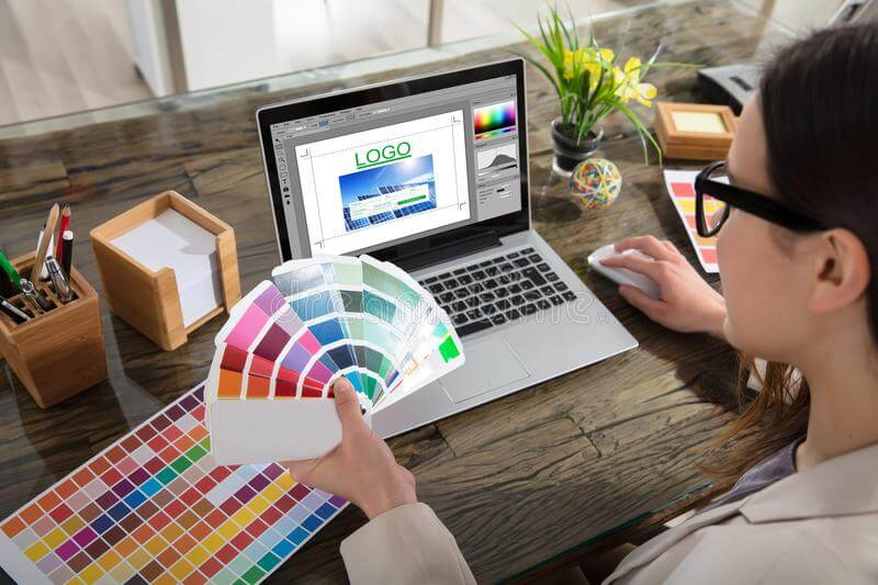 Business-woman-making-color-selection-logo-design-woman-holding-color-swatches-using-laptop-logo-design-software-103319668 Jpg
